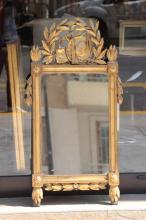 Miroir en bois doré à décor d'attributs paysans en fronton