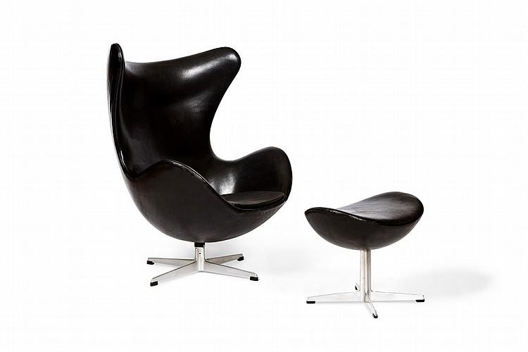 Arne JACOBSEN (1902-1971) -Edition FRITZ HANSEN, 1968  Rare fauteuil et son ottoman, modèle EGG, en cuir, assise pivotante de forme arrondie entièrement gainée de cuir de buffle noir passe poilé reposant sur des piètements en métal de forme profilée cruciforme à réception plate