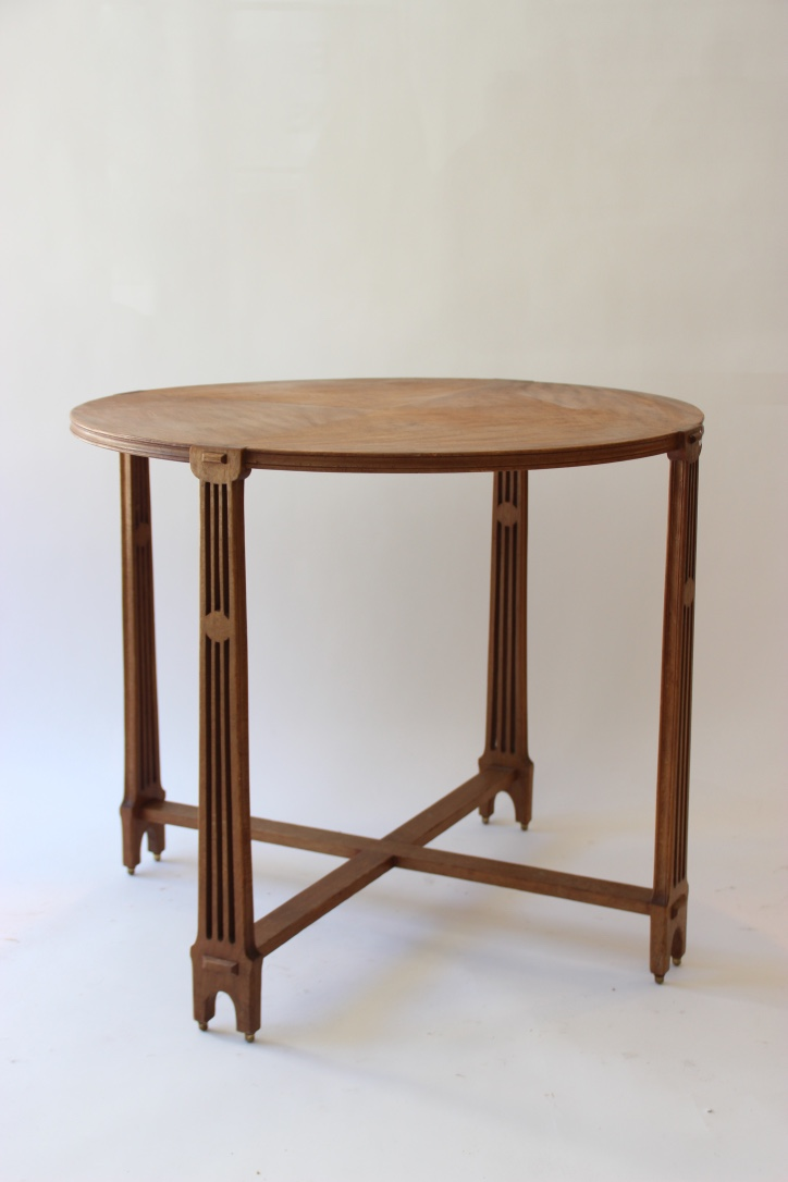 Arts and Craft  Table circulaire en bois de placage reposant sur quatre pieds ajourés se terminant par des petites boules en bronze doré.
