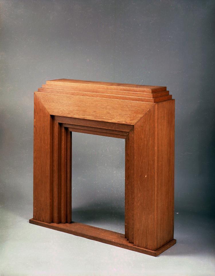 DJO-BOURGEOIS (1898-1937), vers 1935  Cheminée en chêne massif clair, à multiples gradins. L'entrée du foyer reprend le même dessin, inverse. L'ensemble repose sur une base rectangulaire
