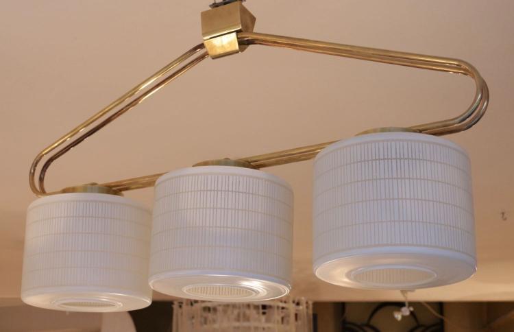 STILNOVO - Vers 1950 Lustre composé d'une armature faite de deux tiges de laiton, reliés entre elles par des cylindres en laiton sur lesquels sont fixés trois globes en verre opalin avec un motif.