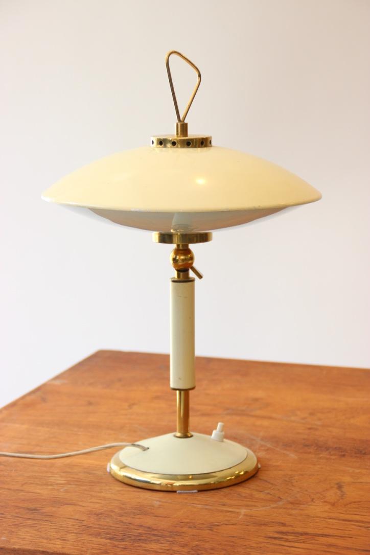 Travail des années 1950  Lampe à poser « soucoupe » en métal laqué crème et laiton à abat-jour circulaire