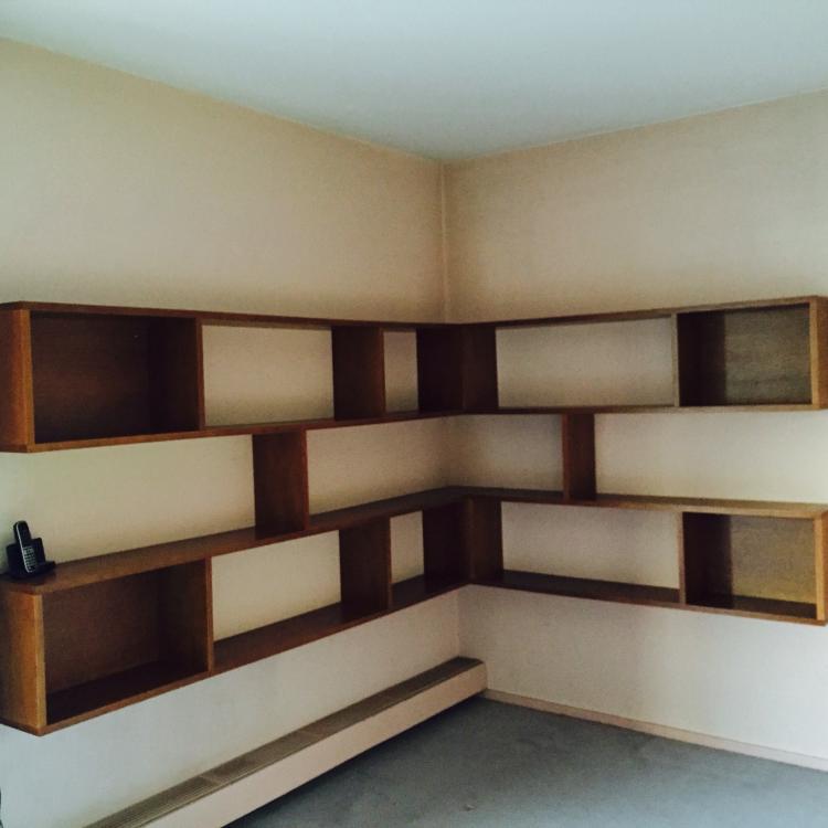 Travail français - Vers 1950  Importante bibliothèque d'angles en chêne et placage de chêne dégageant niches et étagères sur 3 niveaux, composée de deux modules