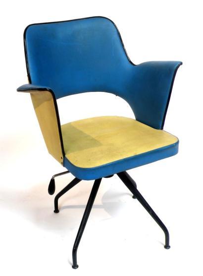 ANONYME, vers 1960  Fauteuil tournant en skaï bleu et jaune soutenu par quatre pied en métal peint en noir.