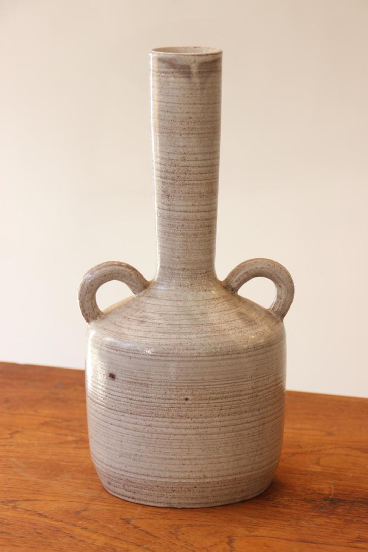GRANDJEAN JOURDAN - VALLAURIS  Vase en terre de faïence rouge à long col rétréci et comportant deux anses latérales. Signé dessous.