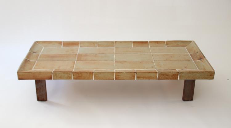 Roger CAPRON (1922-2006)  Table basse rectangulaire à plateau en partie incurvé garni de carreaux de céramique emmaillés bruns, piètement en métal (oxydé)