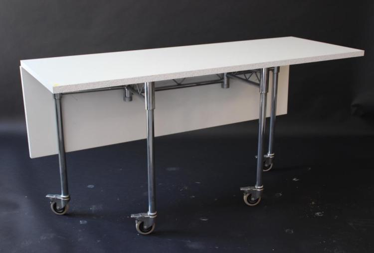 Travail français - vers 1980.  Table-console à géométrie variable en bois mélaminé blanc et moucheté, reposant sur quatre pieds tubulaires en acier chromé à réception sur roues.