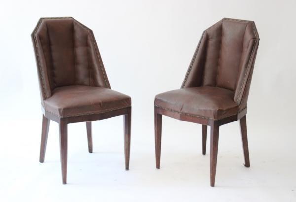 DOMINIQUE, dans le goût de  Paire de fauteuils de style art déco à la forme de tonneaux, recouverts de skaï de couleur brune.
