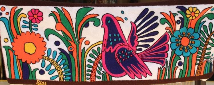Michel REY  Tapisserie brodée figurant un oiseau dans un décor fleuri.