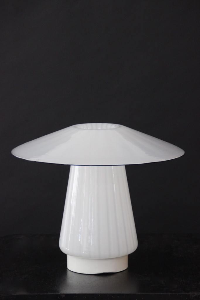 Travail italien - vers 1980.  Lampe à poser en verre soufflé blanc laiteux à décor de stries nuancées, cadre ampoule et piètement solidaires.