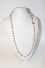 ANONYME  Long sautoir de perles rondes blanches, fermoir bijou en pierre bleue et strass.  Etat d'usage (manque strass au fermoir)  Longueur 73 cm