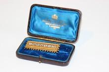 Broche barette en or jaune ornée de 7 brillants et décor de graineti sur le pourtour, fin 19e siècle, dans son écrin   P: 8g