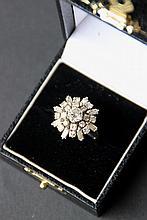 Bague en or blanc ornée d'un diamant central dans un entourage de brillants en forme de fleur.