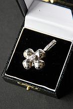 Pendentif de forme trèfle orné d'un diamant en son centre et belière ornée de diamants