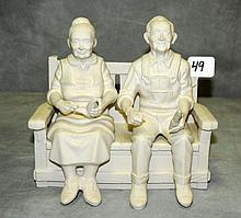 Bisque porcelain figural group of old couple sitting on