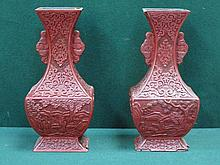 PAIR OF HAND CARVED RED CINNABAR LACQUERED VASES DECORATED WITH ORIENTAL FIGURES WITHIN COUNTRYSIDE SCENES (AT FAULT), APPROXIMATELY 26cm HIGH