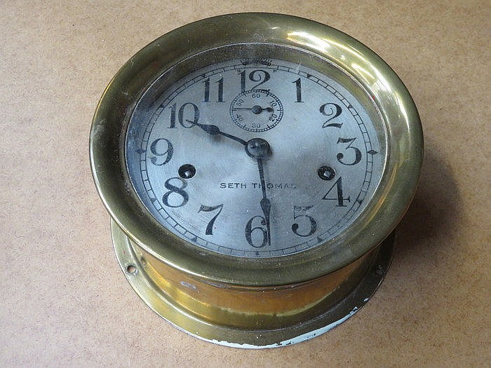ANTIQUE BRASS CIRCULAR SHIPS CLOCK WITH SILVER COLOURED DIAL BY SETH THOMAS