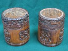 PAIR OF HEAVILY CARVED TREEN AND BAMBOO STORAGE POTS WITH COVERS (AT FAULT)