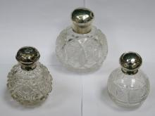 THREE VARIOUS SILVER TOPPED GLASS PERFUME DECANTERS