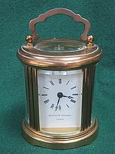 SMALL BRASS OVAL CARRIAGE CLOCK BY MATTHEW NORMAN