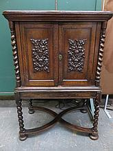 HEAVILY CARVED ANTIQUE OAK TWO DOOR CABINET WITH BARLEY TWIST SUPPORTS AND
