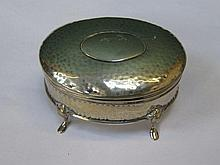 SMALL SILVER HAMMERED OVAL STORAGE BOX WITH COVER ON RAISED SUPPORTS