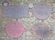 THREE LMS CAST IRON RAILWAY PLAQUES AND NON-RELATED CAST IRON PLAQUE