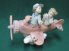 LLADRO GLAZED CERAMIC FIGURE GROUP OF CHILDREN IN A PLANE 17cm