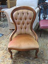 LIGHT OAK CROWN BACK UPHOLSTERED NURSING CHAIR ON BALL AND CLAW SUPPORTS.