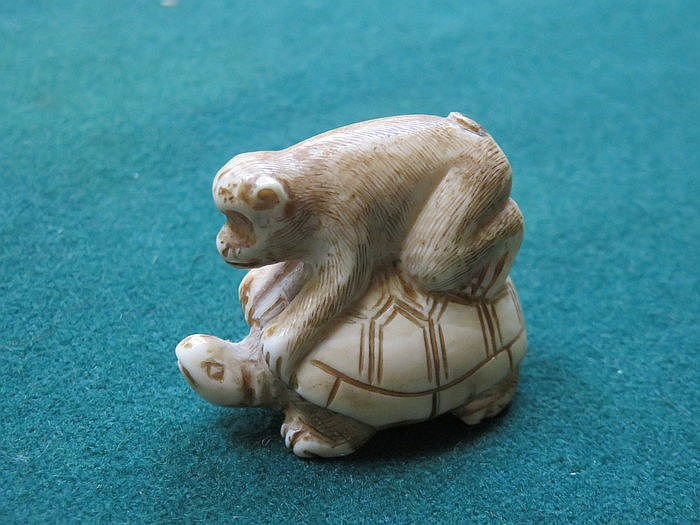 SMALL CARVED IVORY NETSUKE OF A TURTLE WITH MONKEY