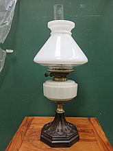 CAST METAL AND BRASS OIL LAMP WITH GLASS RESERVOIR.