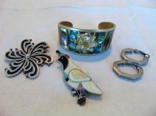 Group of silver jewelry to include: Sterling quale pendant brooch; Mexican Sterling silver pendant brooch (20.2 gm); an abalone and silver bracelet; and a pair of silver earrings.