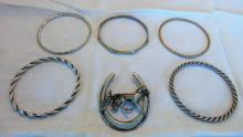 Group of 5 silver bracelets, some signed Sterling (77 gm for bracelets), along with a horseshoe brooch depicting a racing surrey w/horse.