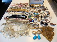 Huge lot of costume jewelry to include: earrings; necklace; jet necklace; gold chains; ladies watch; military insignia; and more.