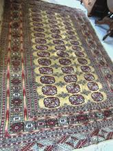 Hand tied middle eastern rug in a geometric pattern in greens, browns, and black