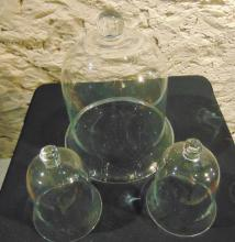 Three hand blown glass bell covers, one large and two small in size