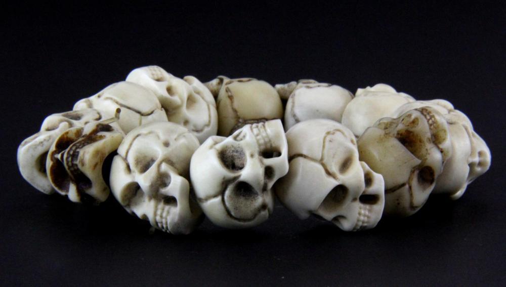 A Group Of Thirteen Tibetan Carved Antler Skull Beads Each