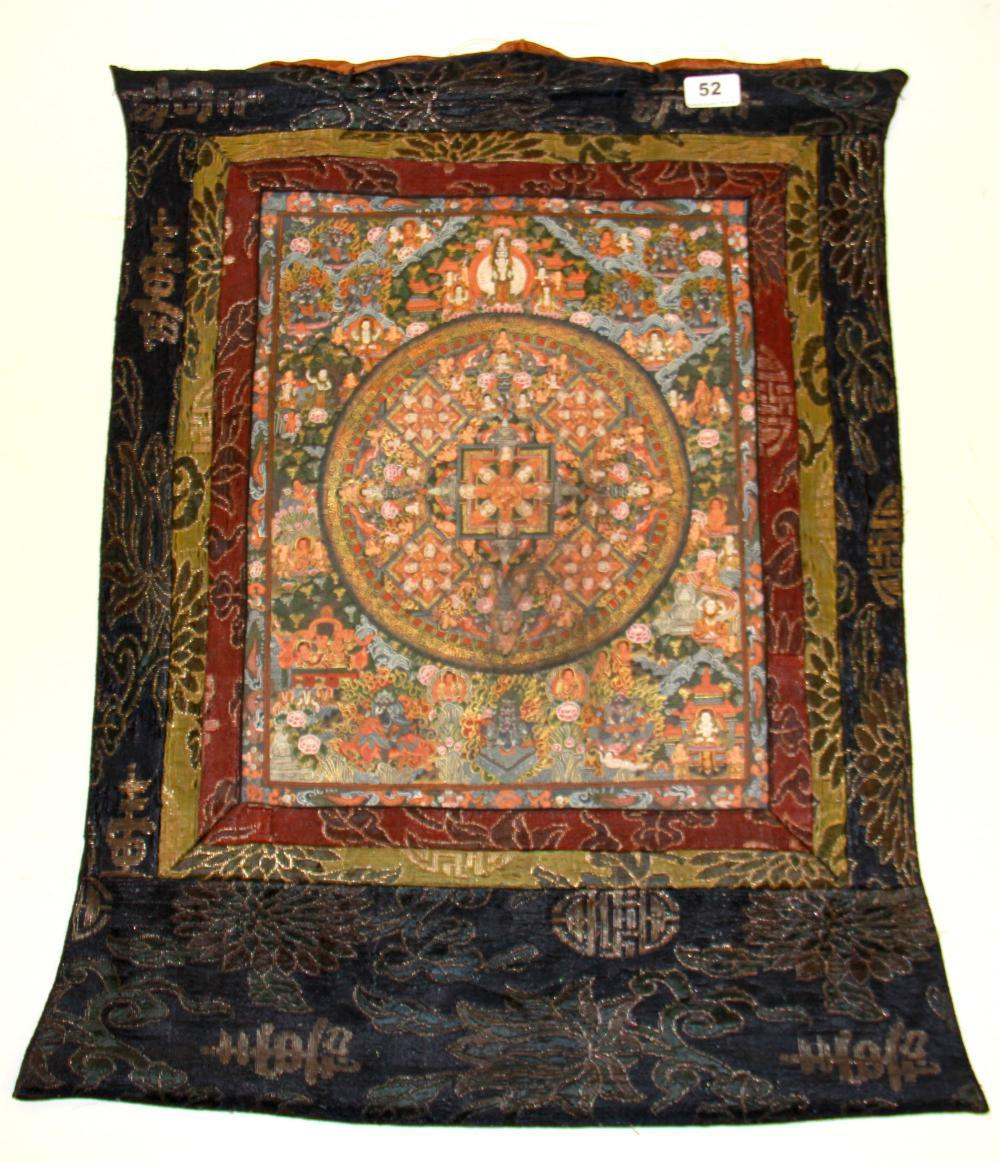 A Tibetan silk mounted hand painted thangka, W. 59cm H. 70cm.