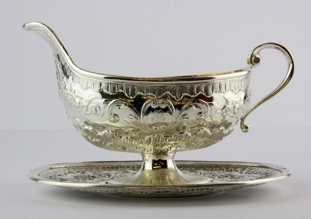 A French hallmarked silver gilt lined sauce boat with attached stand, L. 19cm.
