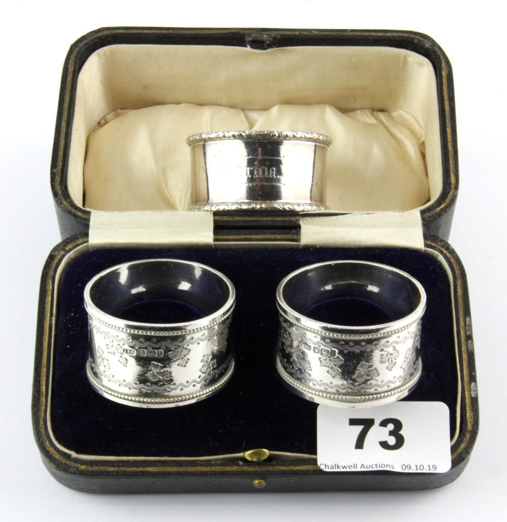 A pair of boxed hallmarked silver napkin rings and a further napkin ring.