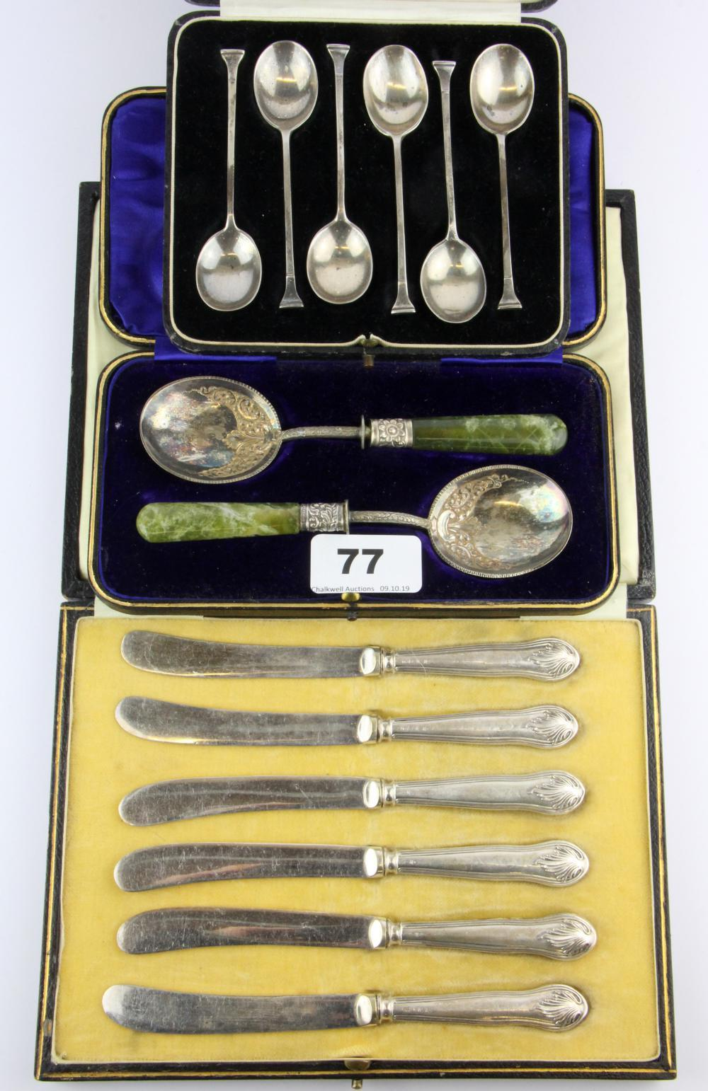 A cased set of six hallmarked silver coffee spoons, six silver handled butter knives and a pair of stone handled serving spoons.