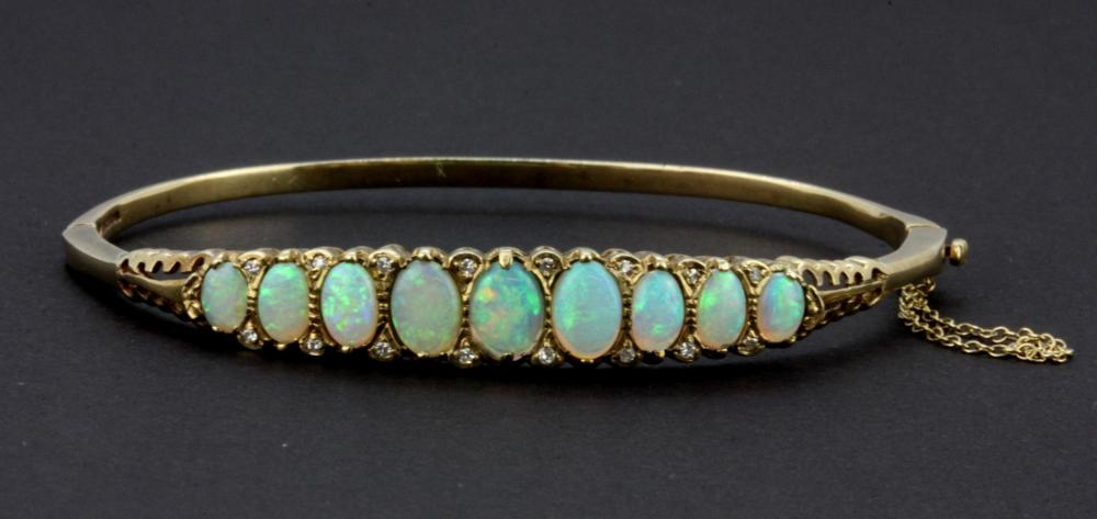 A  9ct gold bangle set with a graduated row of cabochon cut opals interspersed with diamonds. Internal width 6cms, W. 10.7g.