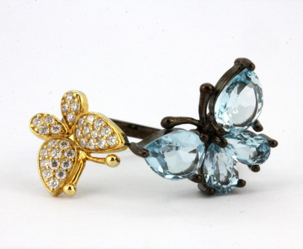 A 925 silver gilt adjustable ring set with pear cut Swiss blue topaz and cubic zirconia.