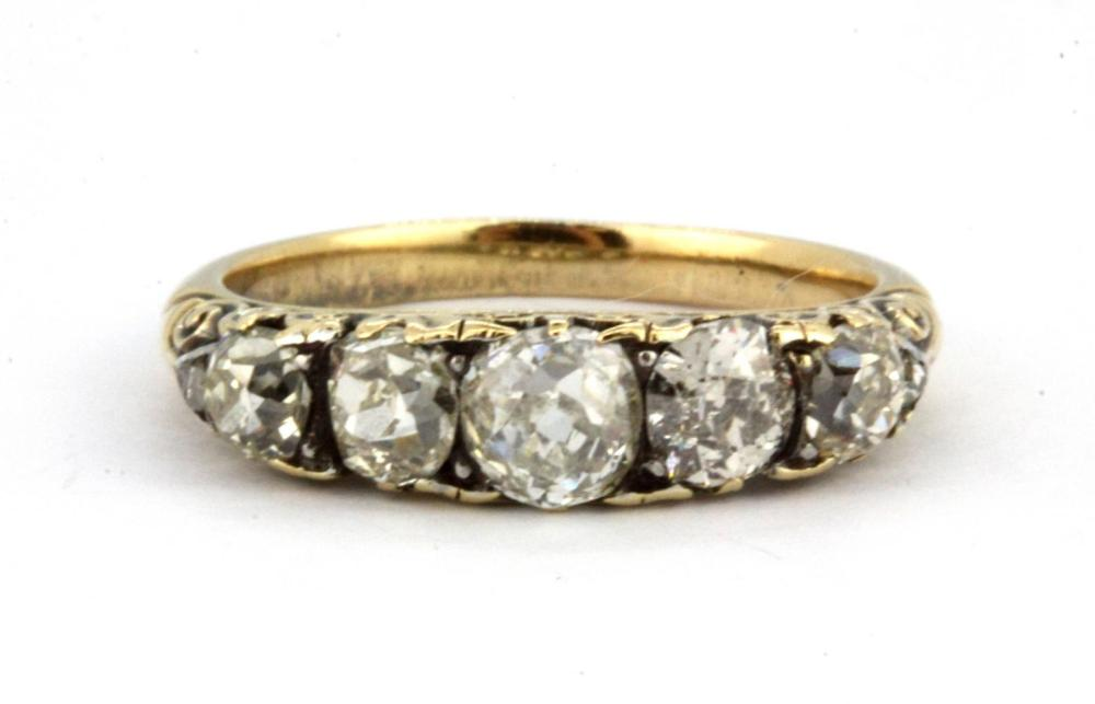 A yellow metal (tested 18ct gold) ring set with five graduated old cut diamonds, (L).
