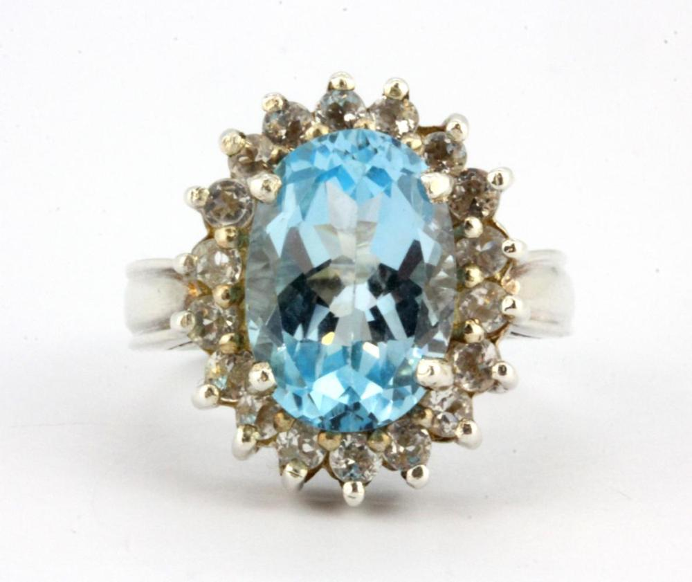 A 925 silver ring set with a large oval cut blue topaz and white stones, (M).