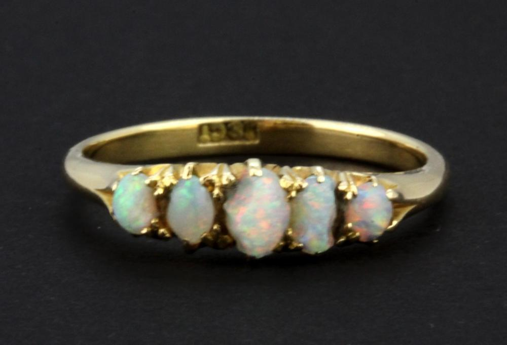 An 18ct yellow gold ring set with five cabochon cut graduated opals, (one opal a/f), (P).