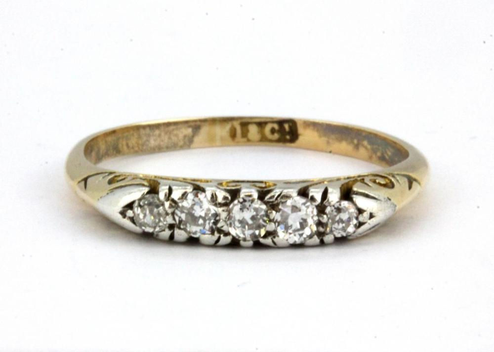 An 18ct yellow gold ring set with five graduated old cut diamonds, (P).