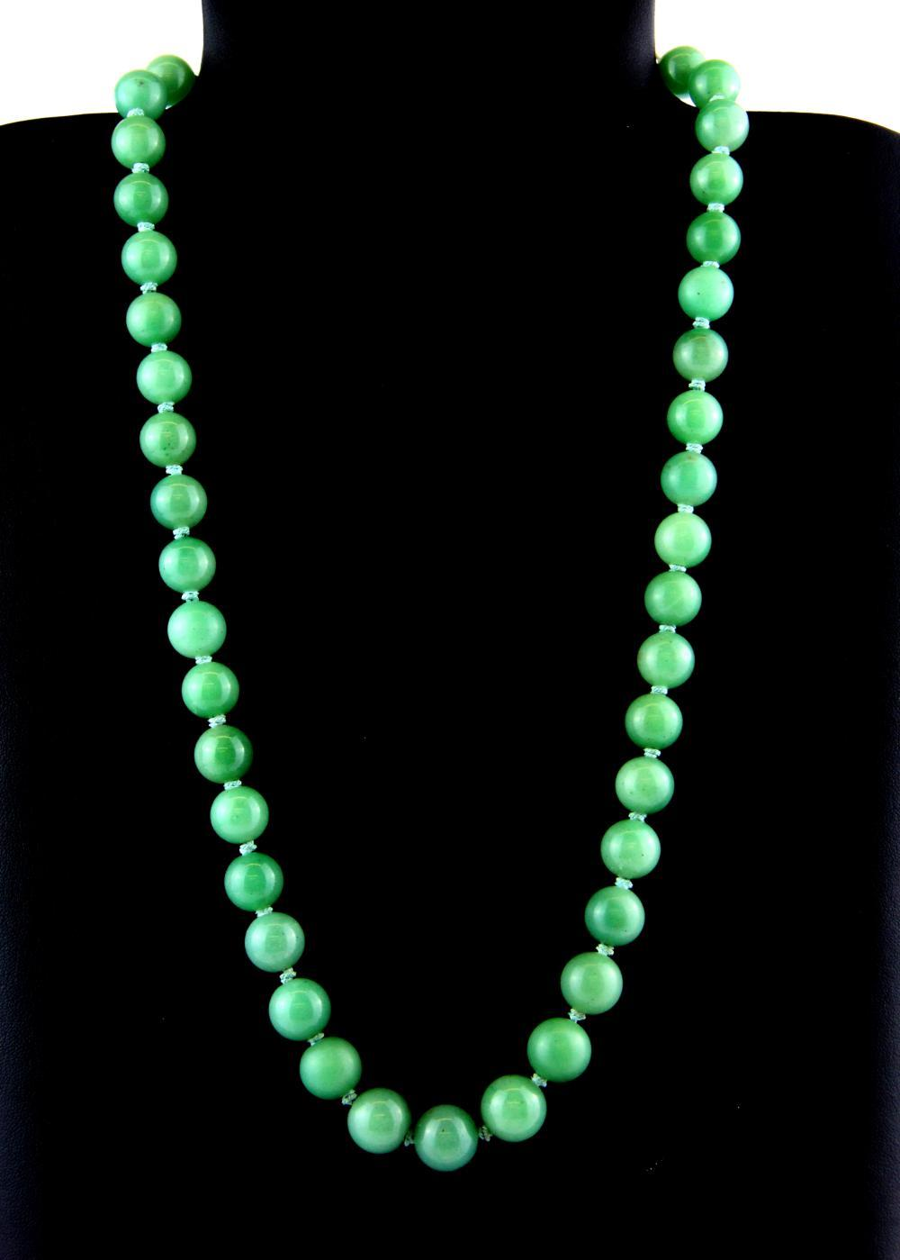 An old Chinese necklace of jade beads on a silver gilt clasp.
