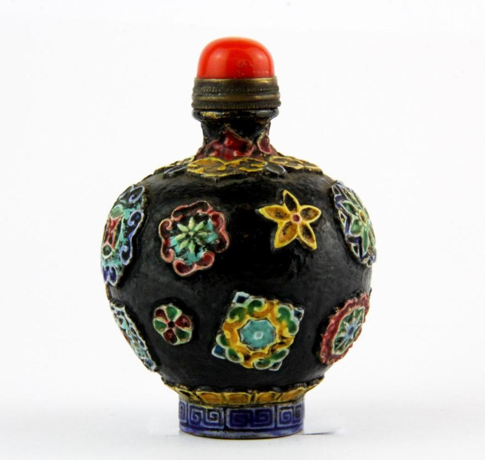 A Chinese relief decorated porcelain snuff bottle with coral stopper, H. 8cm.