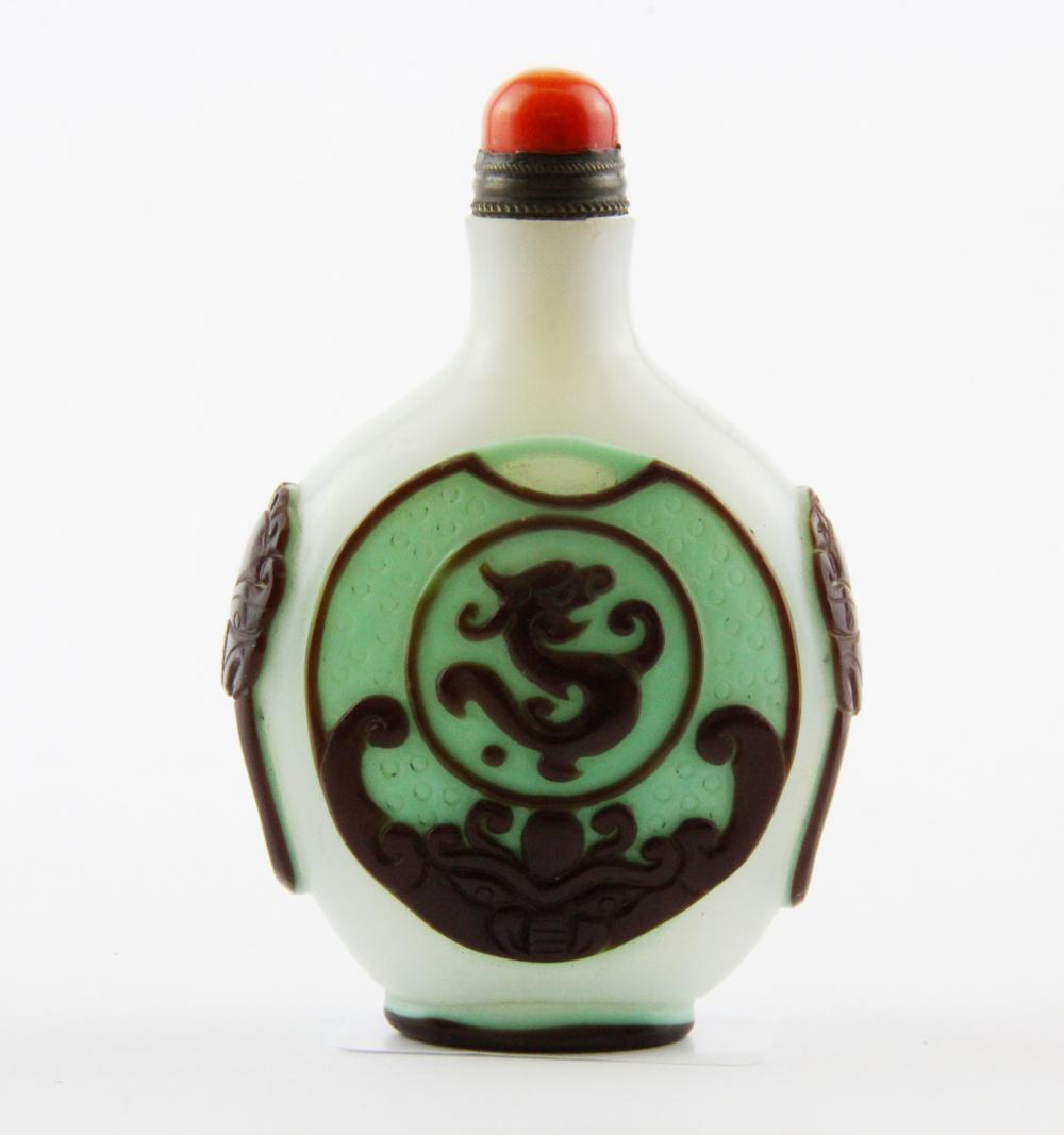 A Chinese carved three colour Peking cameo glass snuff bottle with coral stopper, H. 8.5cm.